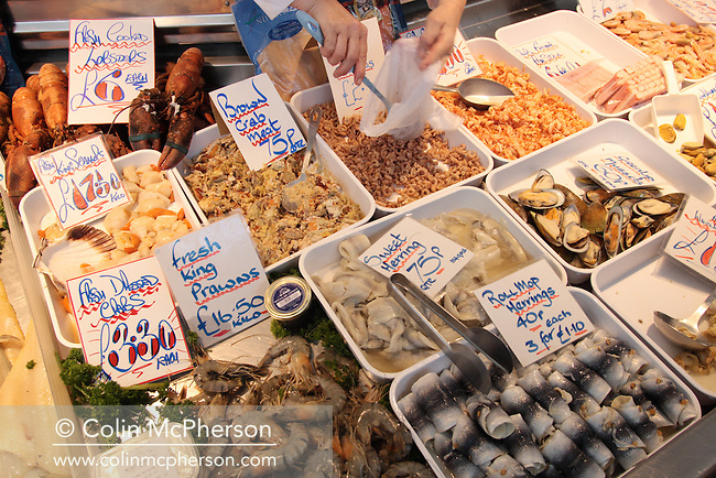 Customers shopping at a fishmongers at Bury market, Lancashire, winner of Best Food Market at the BBC Radio Food and Farming Awards 2008. The market has around 370 separate stalls selling 50,000 different products. It is 200,000 square foot in size and attracts one quarter of a million visitors each week.