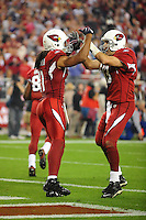 Dec 6, 2009; Glendale, AZ, USA; Arizona Cardinals wide receiver Larry Fitzgerald (left) is congratulated by quarterback Kurt Warner after a first half touchdown against the Minnesota Vikings at University of Phoenix Stadium. The Cardinals defeated the Vikings 30-17. Mandatory Credit: Mark J. Rebilas-