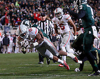 Ohio State Buckeyes running back Ezekiel Elliott (15) dives into the end zone with Michigan State Spartans cornerback Darian Hicks (2) on his back during the fourth quarter of the NCAA football game at Spartan Stadium in East Lansing, Michigan on Nov. 8, 2014. (Adam Cairns / The Columbus Dispatch)