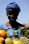 The Gambia. Smiling woman with worn blue dress and turban selling fruit; pineapples and melons.