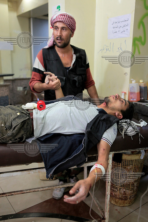 A comrade holds his friends hand as the Free Syrian Army (FSA) fighter, wounded by shrapnel in the neck, lies on a gurney in the Da al-Shfaa Hospital.