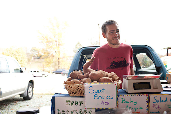 November 23, 2010. Durham, NC.. Sam Hummel, of Ever Laughter Farm, sells sweet potatoes, sausage and other produce at the Durham Farmer's Market holiday sale. Ever Laughter is a small operation but sets aside land for the ever popular sweet potato..   The sweet potato seems to be having a comeback, with many farmers increasing their planting of the potato's numerous varieties, as well as many restaurants including it on their menu in various forms such as the ever popular sweet potato fry.