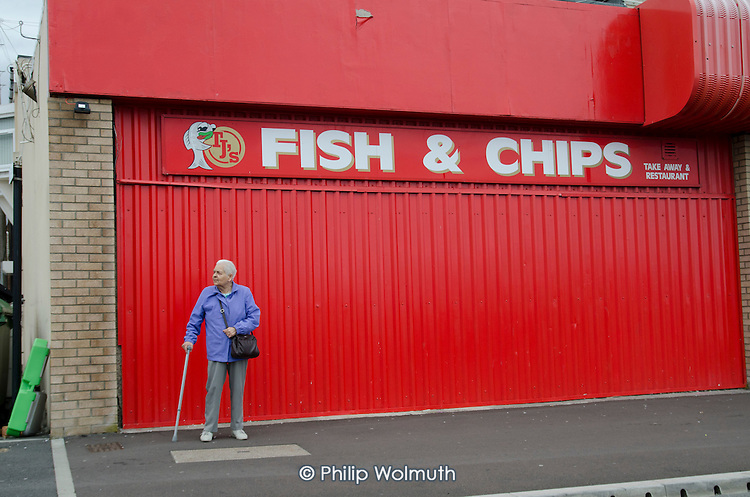 Elderly woman with a walking stick outside a closed fish and chip shop in Seaham, County Durham. Formerly known as Seaham Harbour, the town served as a port for the export of coal until the last local pit closed in 1992.  The harbour now functions at a much reduced level, importing coal from Eastern Europe and elsewhere.