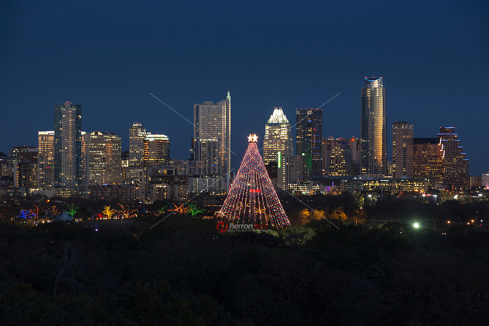 The spectacular Zilker Holiday Tree towers over the Austin Trail of Lights, and the downtown Austin skyline.