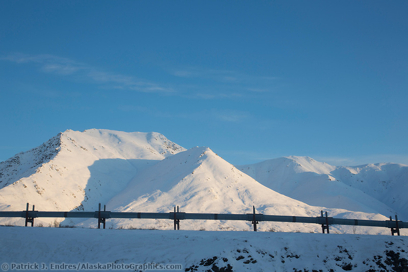 Snow covered Brooks Range mountains and the trans Alaska pipeline near the continental divide in Alaska.