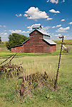 Red wooden barn, clouds, rusting farm machinery, Kansas.