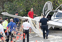 NWA Democrat-Gazette/DAVID GOTTSCHALK  A man (top center) inspects the hood of a small plane after he exited an ambulance as emergency responders secure the scene of a small airplane crash Tuesday, November 3, 2015, on Martin Luther King Boulevard in Fayetteville. Bill Simon, 56, Cliff Slincard, 59, and Maurice Willis, 47, were on the plane that deployed an emergency parachute attached to plane after an attempt at making an emergency landing at Drake Field in Fayetteville. The plane took off from Bentonville airport. All three men were transported to area hospitals with non life threatening injuries.