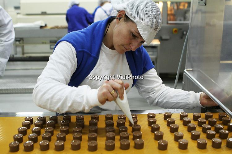 Foto: VidiPhoto..ESSEN - Bij de Nederlands-Belgische chocoladefabriek Ickx in Essen (B) bij Roosendaal (Nl) rollen de lekkerste chocoladeproducten over de lopende band. De chocoladespecialist, levert onder private label aan diverse Nederlandse supermarkten levert. De vraag naar de deels handgemaakte chocoladeproducten van de fabriek-met-drie-gezichten (Ickx, Dragee en Rosenberg)  is zo groot, dat de chocolatterie vorig jaar een omzetstijging van 11 procent wist te boeken. Een deel van de bonbons en andere chocoladeproducten wordt gevuld met handgemaakte Nederlandse jam. Foto: Versiering wordt met de hand aangebracht..