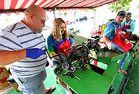 NWA Democrat-Gazette/DAVID GOTTSCHALK Terry Bryson (from left) assists Brianna Cecil, 14, Friday, October 4, 2019, with the use of a vintage apple peeler during the 44th Annual Arkansas Apple Festival on the downtown square in Lincoln. The festival, that runs through Sunday, will feature activities that include a parade, apple core throwing and both bluegrass and gospel music.