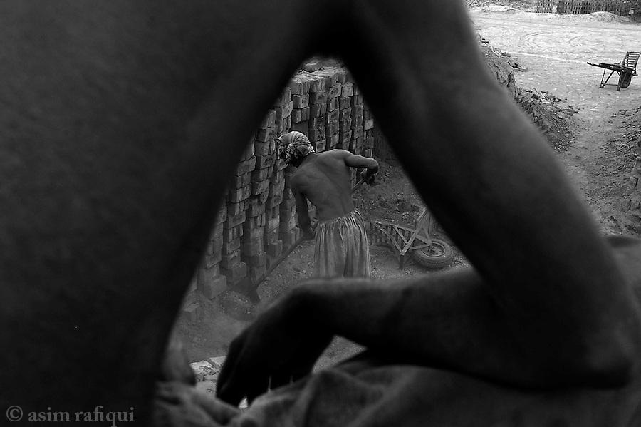 men extract prepared bricks from a pit of a factory.  jalozai, peshawar, pakistan.  september 2003&amp;#xA;&amp;#xA;copyright asim rafiqui 2003<br />