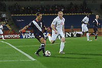 U.S> defender Steve Cherundolo clears the ball from his defensive third under pressure from England's Wayne Rooney. The U.S. and England played to a 1-1 draw in the opening match of Group C play at Rustenburg's Royal Bafokeng Stadium, Saturday, June 12th.