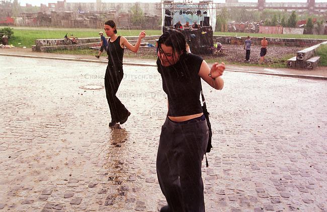 Zwei Maedchen tanzen zu Techno-Musik im stroemenden Regen auf dem Walpurgisnacht-Mauerparkfest in Berlin-Prenzlauerberg.<br /> Organisiert wurde das Fest durch die Berliner Polizei um traditionelle Randale im Bezirk zu verhindern. Da keine Polizeibeamte sichtbar auf und am Fest waren blieb es bis zum Schluss des Festes, in die fruehen Morgenstunden des 1.Mai 2000, ruhig.<br /> 30.4.2000, Berlin<br /> Copyright: Christian-Ditsch.de<br /> [Inhaltsveraendernde Manipulation des Fotos nur nach ausdruecklicher Genehmigung des Fotografen. Vereinbarungen ueber Abtretung von Persoenlichkeitsrechten/Model Release der abgebildeten Person/Personen liegen nicht vor. NO MODEL RELEASE! Nur fuer Redaktionelle Zwecke. Don't publish without copyright Christian-Ditsch.de, Veroeffentlichung nur mit Fotografennennung, sowie gegen Honorar, MwSt. und Beleg. Konto: I N G - D i B a, IBAN DE58500105175400192269, BIC INGDDEFFXXX, Kontakt: post@christian-ditsch.de<br /> Bei der Bearbeitung der Dateiinformationen darf die Urheberkennzeichnung in den EXIF- und  IPTC-Daten nicht entfernt werden, diese sind in digitalen Medien nach &sect;95c UrhG rechtlich gesch&uuml;tzt. Der Urhebervermerk wird gemaess &sect;13 UrhG verlangt.]