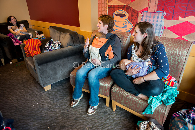 A young woman breastfeeding her baby in a coffee shop while talking to a friend who has her baby asleep in her sling.<br /> <br /> Image from the &quot;We Do It In Public&quot; documentary photography project collection: <br />  www.breastfeedinginpublic.co.uk<br /> <br /> Dorset, England, UK<br /> 17/04/2013