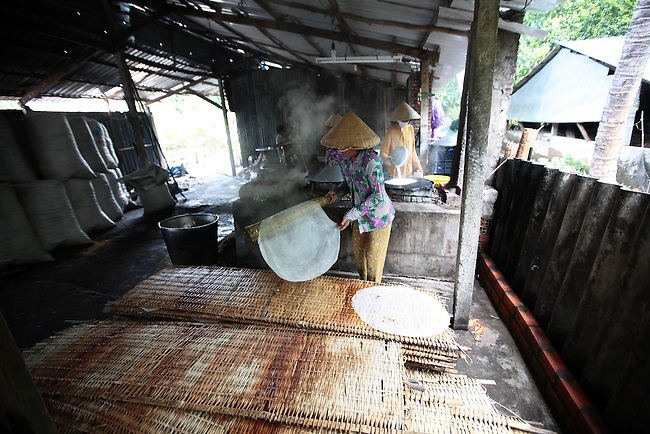 Women make rice noodle sheets at a small factory in the Mekong Delta, south of Can Tho, Vietnam. Sept. 30, 2011.