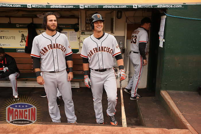 OAKLAND, CA - JULY 7:  Brandon Crawford #35 and Joe Panik #12 of the San Francisco Giants get ready in the dugout before the game against the Oakland Athletics at O.co Coliseum on Monday, July 7, 2014 in Oakland, California. Photo by Brad Mangin