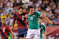 Steve Cherundolo (6)  of the United States and Andres Guardado (18)  of Mexico go up for a header. The men's national teams of the United States (USA) and Mexico (MEX) played to a 1-1 tie during an international friendly at Lincoln Financial Field in Philadelphia, PA, on August 10, 2011.