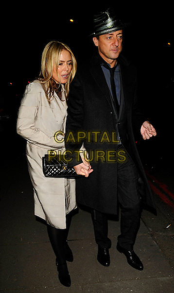 "PATSY KENSIT & JEREMY HEALY .""Hats: An Anthology by Stephen Jones"" Private View, V & A Museum, London, England, February 23rd 2009..Victoria and Albert full length black coat hat quilted Chanel bag hand bag gold cream grey gray .CAP/CAN.©Can Nguyen/Capital Pictures"