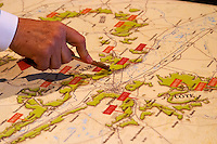 Arnauld Bro de Comeres director of Champagne Deutz showing pointing with the key to the wine cellar the location of Champagne Deutz and Ay on an old map at Champagne Deutz in Ay, Vallee de la Marne, Champagne, Marne, Ardennes, France, low light grainy grain