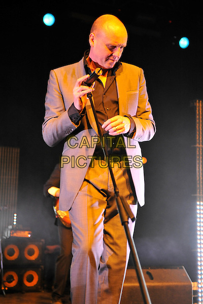 HEAVEN 17- Glenn Gregory.Heaven 17 performs on stage at HMV Forum, London, England. .November 28th, 2010.stage concert live gig performance music half length brown beige suit 3/4 looking down.CAP/MAR.© Martin Harris/Capital Pictures.