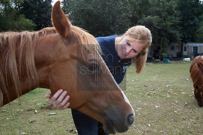 Kimberly Kelly, South Carolina state director for The HSUS, greets a horse during a raid on a puppy mill in Johnston, SC on Tuesday, Sept. 11, 2012. HSUS workers found over 200 dogs, nine horses and 30-40 fowl.