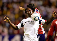 Patrick Nyarko (w) forward of Chicago Fire traps a ball in front of CD Chivas USA midfielder and captain Jonathan Bornstein (13-red). The Chicago Fire defeated CD Chivas USA 3-1 at Home Depot Center stadium in Carson, California on Saturday October 23, 2010.