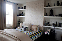 A guest bedroom houses more of Ben de Lisi's ceramic collection, displayed on open shelves either side of the bed