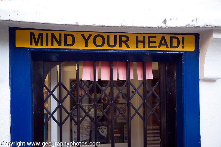 Mind Your Head sign on low shop doorway