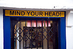 Mind Your Head sign on low shop doorway