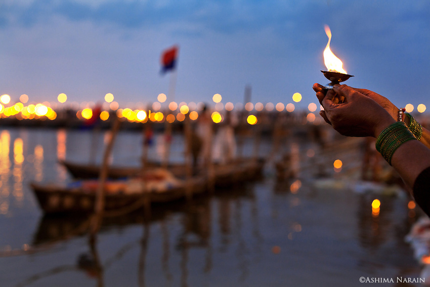 Maha Kumbh Mela, Allahbad, 24th February 2013 -  A Pilgrim does a small arti at the banks of the Ganga at sunset, a day before the Maghi Poornima (full moon) Snan.