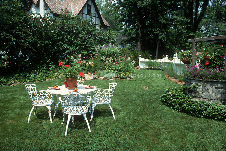 Summer Garden with white wrought iron furniture table and chairs, lawn  grass and house,