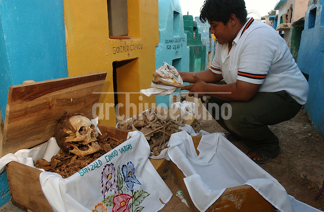 Ruben Cohuoo, 18,  cleanthe grave and rearranging the bones of his grandparents in Pomuch Town, in the northwestern Yucatan Peninsula, Mexico, Friday, Oct 29, 2004. In this small village , the last days of October are devoted to cleaning the bones: dusting, polishing, scrubbing and rearranging the skeletal remains of family members in time for the Day of the Dead, when Mexicans welcome the souls of the dearly departed back to earth.