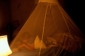 Zambia. Tourist on safari sleeping under a mosquito net.