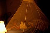 Zambia. Tourist on safari sleeping under a mosquito net.