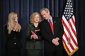 "US President Bush leans over to chat with Vicki Lazear, wife of Eddie Lazear who was just sworn in as Chairman of the Council of Economic Advisors at the EEOB in Washington DC March 6, 2006. Lazear's daughter Julia ""Julie"" at left. <br /> Credit: Ken Cedeno / Pool via CNP"