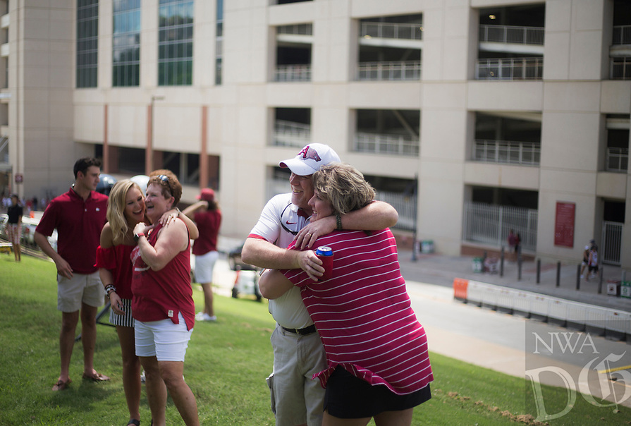NWA Democrat-Gazette/CHARLIE KAIJO Ed and Kim Pinter of North Little Rock (center) hug while taking a picture during a tailgate before the game against the Eastern Illinois Panthers, Saturday, September 1, 2018 at Razorback Stadium in Fayetteville.