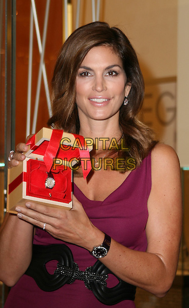 CINDY CRAWFORD .at a photocall to launch the new Omega watch collection at Westfield Shopping Centre, London, England, UK, .October 15th 2009.half length holding wrist watch box black waist belt sleeveless purple silver clear stone necklace earrings matching .CAP/JIL.©Jill Mayhew/Capital Pictures