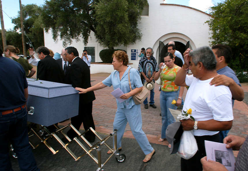 Isabel Abalos, center, reaches out to touch the casket of Lucresia Dominguez Luna as Luna's father, Cesario Dominguez, right, wipes tears from his eyes at St. Mark's Presbyterian Church in Tucson on Friday, July 29, 2005. Luna died while crossing into the U.S. through the Arizona desert. Dominguez spent weeks searching southern Arizona for her body.
