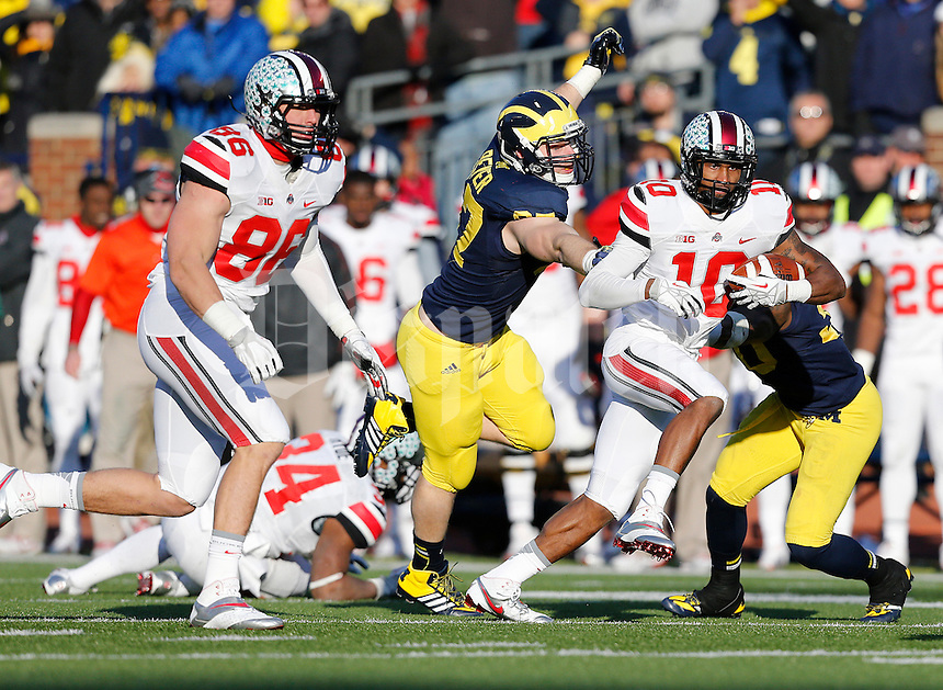 Ohio State Buckeyes wide receiver Philly Brown (10) dodges a tackle from Michigan Wolverines linebacker Brennen Beyer (97) in the fourth quarter of the college football game between the Ohio State Buckeyes and the Michigan Wolverines at Michigan Stadium in Ann Arbor, Michigan Saturday afternoon, November 30, 2013. The Ohio State Buckeyes defeated the Michigan Wolverines 42 - 41. (The Columbus Dispatch / Eamon Queeney)