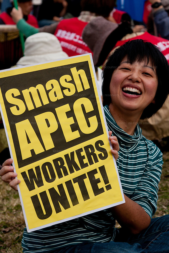 A woman holds an anti-APEC sign at an Anti APEC (Asia Pacific Economic Conference)  Demo by left-wing activist groups and trade unions in Yokohama, Japan Sunday, November 14th 2010