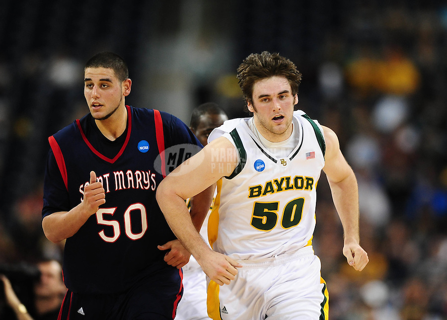 Mar 26, 2010; Houston, TX, USA; Baylor Bears center Josh Lomers (right) against St. Marys Gaels center Omar Samhan during the semifinals of the south regional in the 2010 NCAA mens basketball tournament at Reliant Stadium.  Mandatory Credit: Mark J. Rebilas-