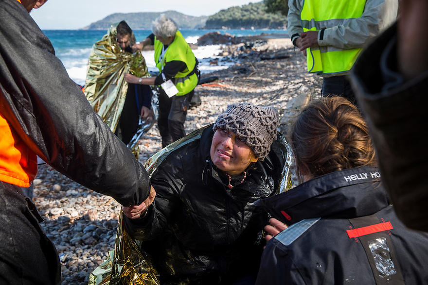 October 31, volunteers attend to people during the moments after their arrival to the island of Lesbos during a day with high winds and dangerous sea conditions.