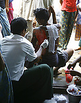 A Cyclone Nargis survivor receives treatment at a makeshift medical station at the town of Labutta, in Irrawaddy Division, May 10, 2008. Despairing survivors in Myanmar awaited emergency relief on Friday, a week after 100,000 people were feared killed as the cyclone roared across the farms and villages of the low-lying Irrawaddy delta region. The storm is the most devastating one to hit Asia since 1991, when 143,000 people were killed in neighboring Bangladesh. Photo by Eyal Warshavsky  *** Local Caption *** ëì äæëåéåú ùîåøåú ìàéì åøùáñ÷é àéï ìòùåú áúîåðåú ùéîåù ììà àéùåø