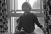 Two kids hanging out in the window of one of the bedrooms, Summerhill school, Leiston, Suffolk, UK. 1968.
