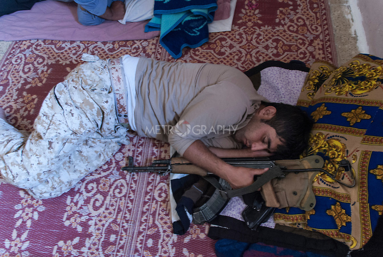 13/08/14  Iraq -- Daquq, Iraq -- A peshmerga sleeps with his gun at the base in Daquq.