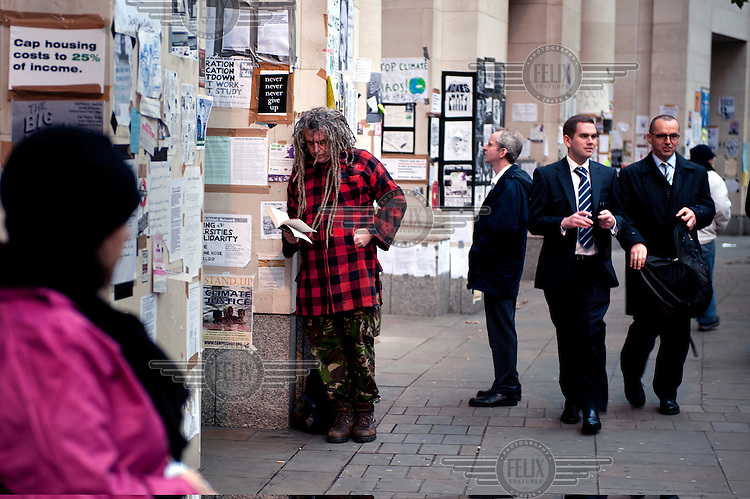 A protestor reads a book next to a wall covered in activist's posters and flyers. It is next to the Occupy London protest camp at St Paul's Cathedral in the City of London. The protest is part of a worldwide movement against the banking industry and the prevailing economic system..