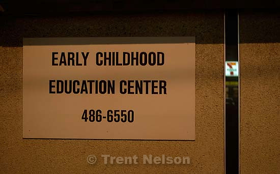 Early Childhood Education Center sign with 7-11 logo reflected in window. 10/14/2001, 8:22:21 PM<br />