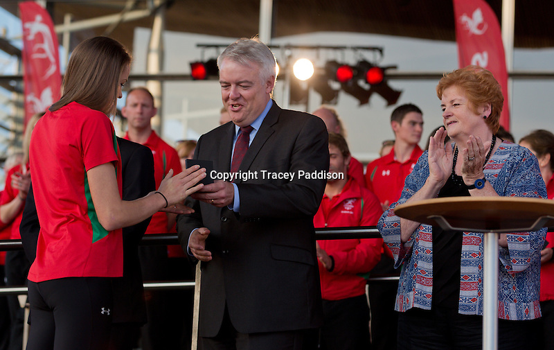 First Minister of Wales Carwyn Jones presents gymnast Frankie Jones with a specially commissioned medal from the Royal Mint at the Team Wales Commonwealth Games Homecoming Ceremony at the Senedd, Cardiff Bay, Wales, United Kingdom 10th September 2014.