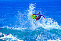 Surfer flies off the lip of a wave at a beach on Maui.