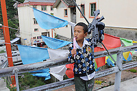A young boy with a toy gun in the town of Heishui on the south-east edge of the Tibetan Plateau in Sichuan Province, western China.
