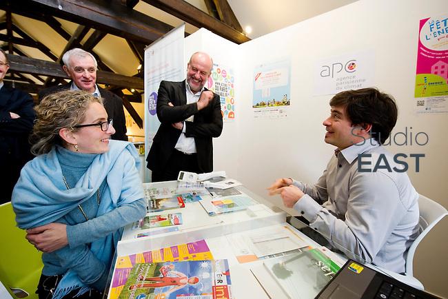 Mme Delphine Batho (gauche, écharpe bleue), ministre de l'environnement et de l'énergie, écoute les conseils d'un conseiller pour réduire sa consommation d'énergie, sous l'oeil de Bruno Léchevin (centre), à l'Agence Parisienne du Climat (ACP), dans le parc de Bercy, à Paris, France, le 30 mars 2013. Photo : Lucas Schifres